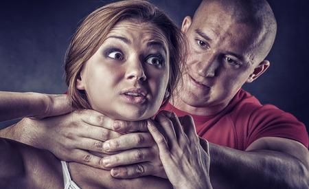 violencia intrafamiliar: Mujer La violencia dom�stica abusada y estrangulada por el hombre fuerte