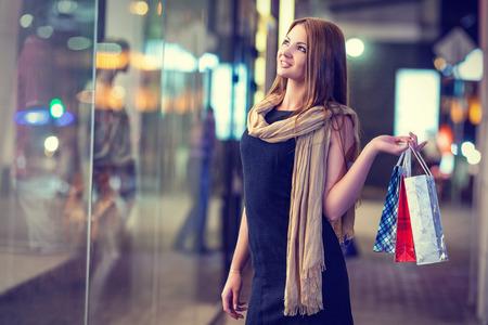 chicas de compras: Mujer hermosa que lleva muchas bolsas de la compra en una calle de la ciudad Foto de archivo