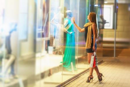 chicas comprando: Mujer hermosa que lleva muchas bolsas de la compra en una calle de la ciudad Foto de archivo