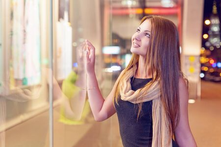 woman looking: Smiling young woman shopping at an outdoor mall