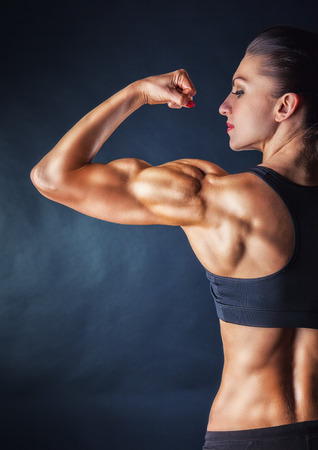 muscle girl: Athletic young woman showing muscles of the back and hands on a black background Stock Photo