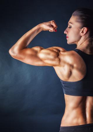 Sportlich junge Frau, die Muskeln des Rückens und die Hände auf schwarzem Hintergrund Standard-Bild - 42303327