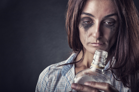 intoxicated: Young beautiful woman in depression, drinking alcohol on a dark background