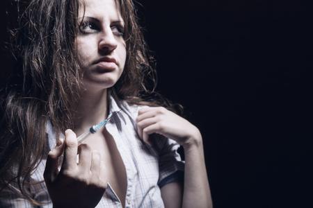 droga: Mujer joven con la drogadicci�n en el Focus background? oscuro en la jeringa