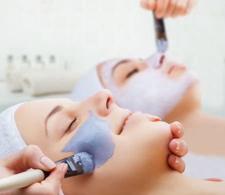 mujer maquillandose: Utilice una mascarilla para la cara dos mujeres jóvenes en un salón de belleza