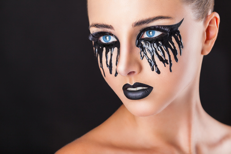 Closeup of a beautiful woman with fantasy makeup with black tears and lips on a black background