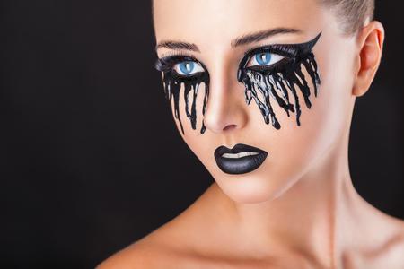 maquillaje de fantasia: Primer plano de una mujer hermosa con maquillaje de fantas�a con l�grimas negras y los labios sobre un fondo negro