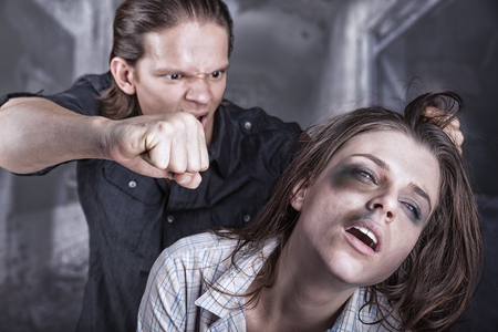 violencia: Mujer víctima de violencia doméstica y el abuso. Un hombre golpea a una mujer joven