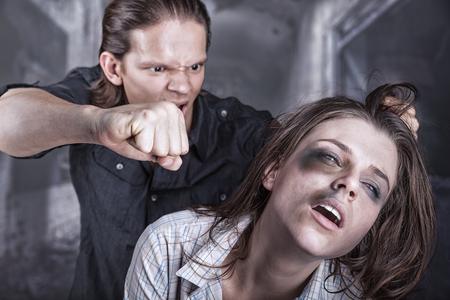 Vrouw slachtoffer van huiselijk geweld en misbruik. Een man slaat een jonge vrouw Stockfoto