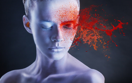 paint splash: White face with red spray paint on a white background. Fashion makeup Stock Photo