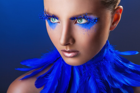 maquillaje fantasia: Mujer joven atractiva con maquillaje con plumas azules brillantes sobre un fondo azul Foto de archivo