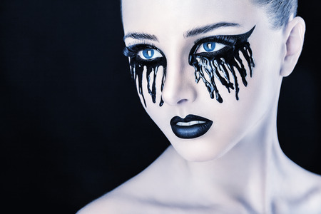 fantasy makeup: Closeup of a beautiful woman with fantasy makeup with black tears and lips on a black background