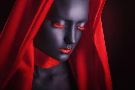 femme noire nue: Jeune femme dans une cape rouge avec le maquillage noir sur un fond sombre Banque d'images