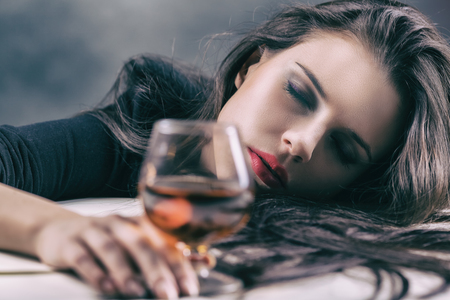 abuse young woman: Young beautiful woman drinking alcohol on dark background. Focus on woman Stock Photo