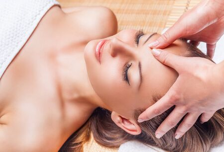 woman naked body: Beautiful young woman receiving facial massage with closed eyes in a spa salon
