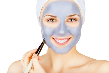 Beautiful young woman doing cosmetic mask on her face isolated on white background Stock Photo