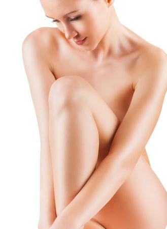 mujer desnuda sentada: Primer plano de una hermosa mujer desnuda joven aislado en un fondo blanco Foto de archivo