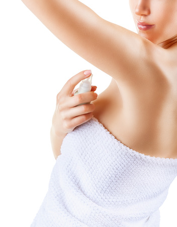 Close up of woman applying deodorant on underarm isolated on a white background