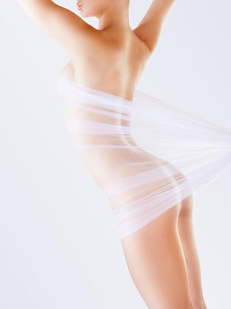 mujer sexy desnuda: El cuerpo de una mujer desnuda a través de la tela transparente sobre un fondo claro Foto de archivo