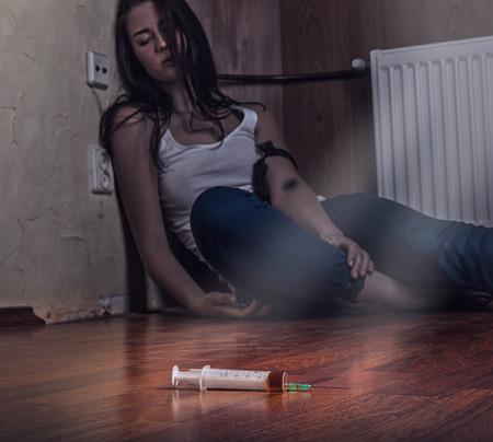 droga: Primer plano en el suelo de la jeringa con el medicamento. En el fondo, un joven drogadicto