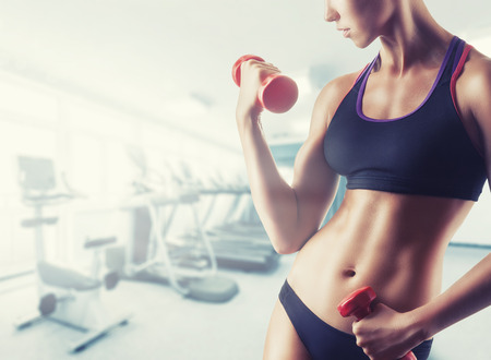 beautiful woman body: Close-up of a young woman exercising with weights in the gym Stock Photo