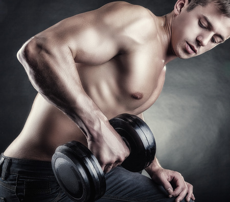 powerfully: Close-up of a muscular young man lifting weights on dark background