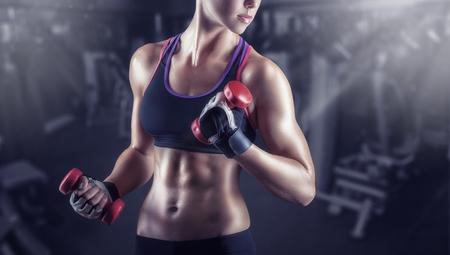 pesas: Primer plano de una mujer joven el ejercicio con pesas en el gimnasio