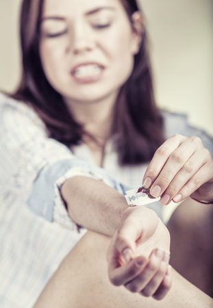 lacerate: Young woman cuts veins on a hand. Focus on hand