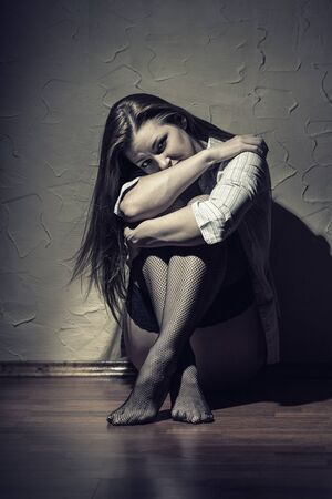 young woman sitting: Sad young woman sitting alone in a empty room