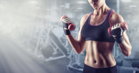 Close-up of a young woman exercising with weights in the gym Stock Photo