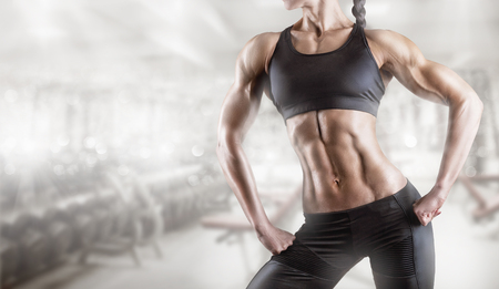 Close-up of a woman's body bodybuilder in the gym