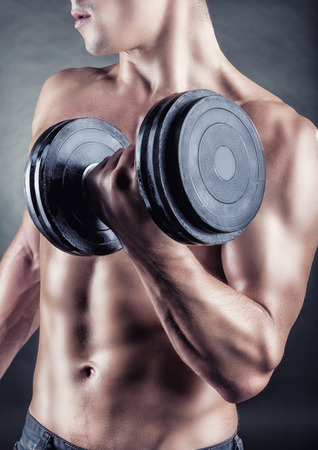 powerfully: Young muscular man with dumbbells on a black background