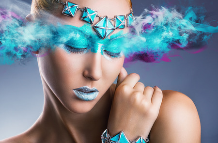 maquillaje de fantasia: Mujer joven con maquillaje verde colorido con el humo multicolor