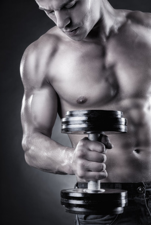 powerfully: Closeup of a muscular young man lifting weights on dark background Stock Photo