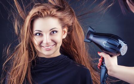 peluquería: Primer plano de las manos de peluquería secado de pelo largo con secador de pelo sobre un fondo oscuro