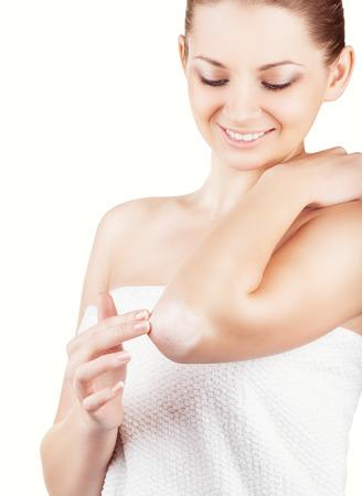 codo: Primer plano de una mujer se hace cargo de los codos usando crema cosmética aislado en un fondo blanco Foto de archivo