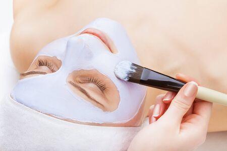 face mask: Applying facial mask at woman face at beauty salon