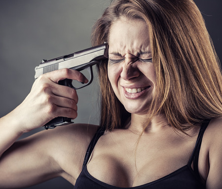Woman with pistol pointing on her head Stock Photo