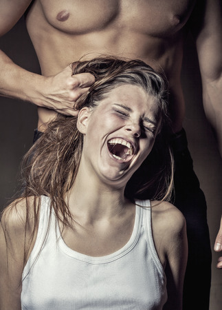 victim: Man pulls a young womans hair. Woman victim of domestic violence and abuse Stock Photo