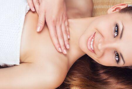 corps femme nue: Belle jeune femme recevant un massage du visage et du cou dans un salon de spa