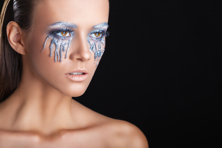 bright colors: Closeup of a beautiful woman with fantasy makeup with gray tears on black background