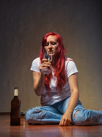 liquor girl: A young woman from a bottle of wine-drinking at home sitting on the floor
