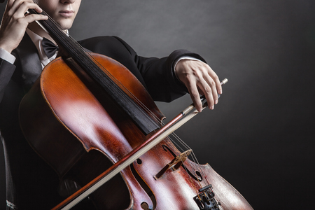 cellos: Close-up of cellist playing classical music on cello on black background Stock Photo