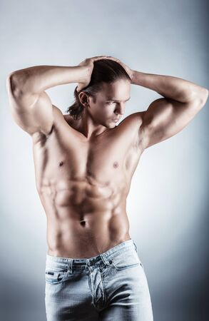 naked male body: Healthy muscular young man on a gray background