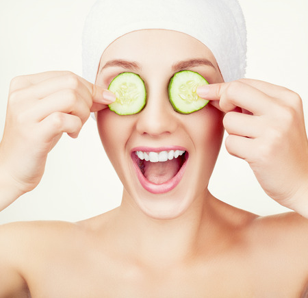 woman eye: Beautiful young woman holding cucumber slices on her eyes Stock Photo