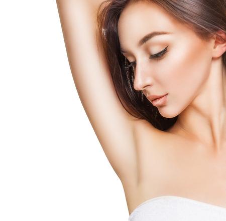 axila: Primer plano de una mujer joven hermosa que muestra su axila suave aislado en el fondo blanco