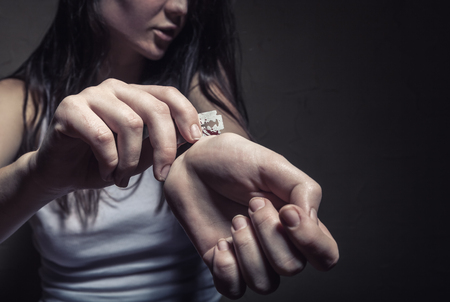 lacerate: Young woman cuts veins on a hand on a dark background. Focus on hand