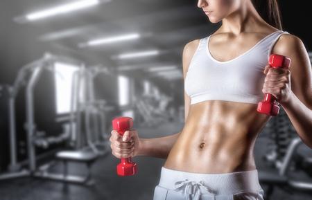 Primer plano de una mujer joven el ejercicio con pesas en el gimnasio
