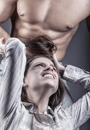 domestico: El hombre tira el cabello de una mujer joven. La mujer víctima de la violencia doméstica y el abuso