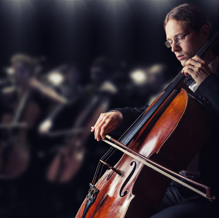 cellist: Close-up of cellist playing classical music on cello in the orchestra